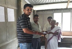 First Applicant of Jalukbari NSK, a senior citizen receives her acknowledgement slip from the NSK staff on 16th June, 2015.
